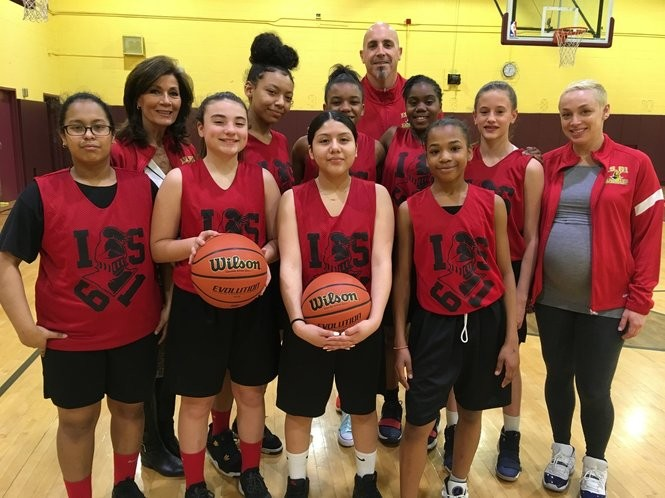 Members of the Lady Knights basketball team are joined by Principal Susan Tronolone, second from left, and teachers Kevin Heiden, in back, and Erin Kyle, at right. (Staten Island Advance/Claire Regan)