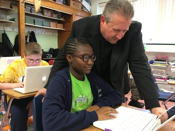 Pastor Michael Bagnall assists St. John's Lutheran eighth-grader Yvonne Clinton, who will attend Curtis High School in the fall. (Staten Island Advance/Claire Regan)