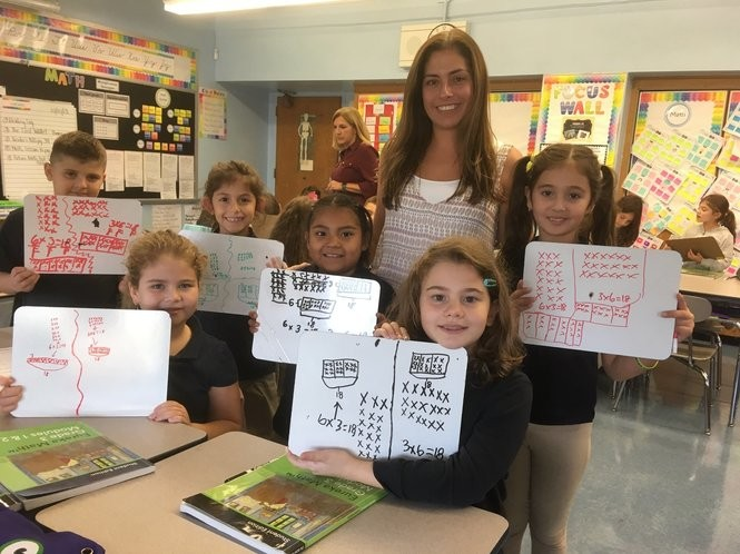 Third-grade teacher Stephanie Cannizzaro joins students as they display their math projects. From left are Florian Muja, Tiana Mujezic, Alisa Beshiri, Yareli Herrera, Lorina Fazliu and Sofia Jahovic. (Staten Island Advance/Claire Regan)