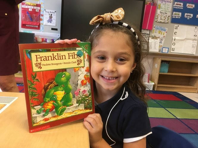PS 52 kindergartner Amaia Maliqi holds up one of her favorite books. (Staten Island Advance/Claire Regan)