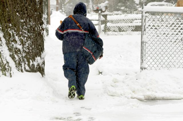 St. George Letter Carrier Chin Jan Delivers mail as snow starts to get heavy during the 2010 blizzard (Advance File Photo)