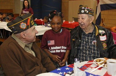 St. Adalbert School hosted its Veterans' Breakfast and Assembly on Nov. 6, 2014. World War II veterans Frank Bradicich, left, and Roy Ferlazzo -- both of Eltingville -- talk to student Deanah Sylvain. (Staten Island Advance/Irving Silverstein)