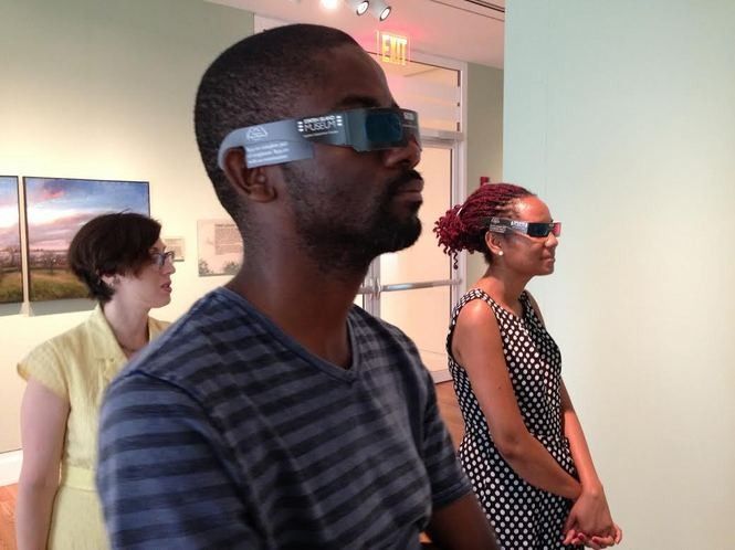 """Amanda Straniere, left, Staten Island Museum community campaign coordinator, looks on as African fellows Butholezwe Kgosi Nyathi of Zimbabwe and Juby Kgomotso Peacock of Botswana wear anaglyph glasses to watch the art film, """"SI3D."""" (Claire Regan/Staten Island Advance)"""