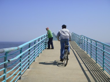 A bicyclist rides by George Browne, left, of Huguenot, as he enjoys his first day back at the Dorothy Fitzpatrick Fishing Pier in Lemon Creek Park. Closed for months following Hurricane Sandy, it reopened at the end of last month.