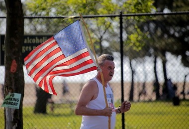 Morning light illuminates the American flag carried by a runner during the Staten Island Advance Memorial Day Run. Monday May 26, 2014.