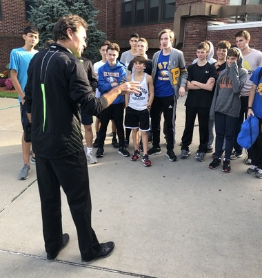 Rod Dixon speaks with members of the St. Peter's high school boys Cross-Country team.