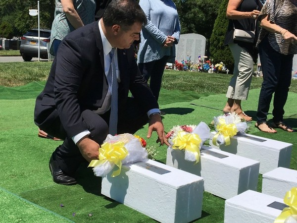 In this 2017 photo, Public Administrator Anthony Catalano says a prayer for the six stillborn babies at Resurrection Cemetery in Pleasant Plains. (Staten Island Advance/Annalise Knudson)