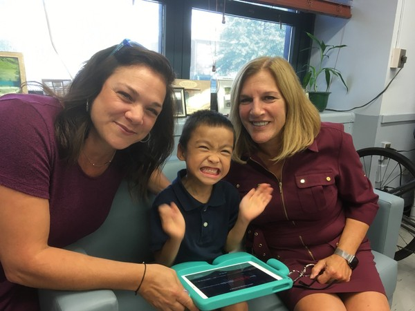 First-grader Aidan Sylvester is happy to visit with PS 52 Assistant Principal JoAnne Cancel and Principal Jane McCord as he explores maps on his iPad. (Staten Island Advance/Claire Regan)