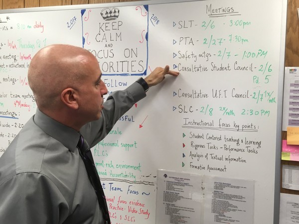 On a giant dry erase board behind his desk, Principal Joseph Scarmato keeps track of his appointments and priorities.
