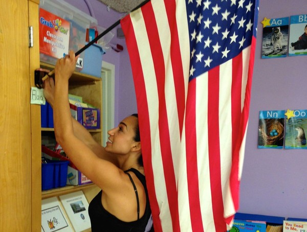 In this 2015 file photo, Kristy Buccafusco, a kindergarten teacher at PS 69, New Springville, puts up the American flag in her classroom in preparation for a 9/11 lesson on how to salute the flag and what the Pledge of Allegiance means.