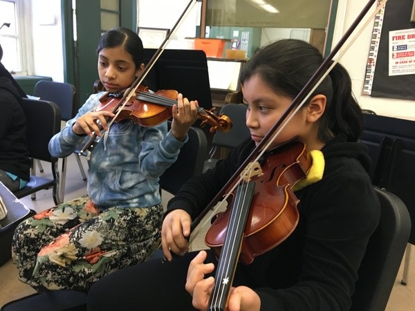 Sixth-graders Rubi Rios, left, and Jasmine Mendoza concentrate during strings class at Morris Intermediate School, Brighton Heights. (Staten Island Advance/Claire Regan)