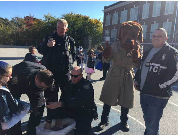 Police officers from the 123rd Precinct and mascot McGruff distribute Halloween bags after the Halloween Safety Tips workshop at PS 42 in Eltingville last year.