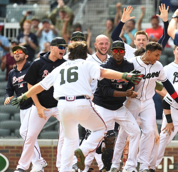 ATLANTA, GA. - MAY 28: Charlie Culberson #16 of the Atlanta Braves is mobbed by teammates after hitting a pinch-hit, two-run walk-off home run in the ninth inning against the New York Mets at SunTrust Field on May 19, 2018 in Atlanta, Georgia. (Photo by Scott Cunningham/Getty Images)