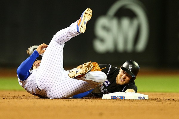Pat Valaika #4 of the Colorado Rockies slides in safely after tagging up from first base ahead of the tag from Asdrubal Cabrera #13 of the New York Mets at Citi Field on May 5, 2018. (Photo by Mike Stobe/Getty Images)