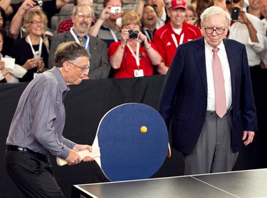 """FILE - In this May 6, 2012 file photo, Warren Buffett, chairman and CEO of Berkshire Hathaway, right, watches Bill Gates use an oversize paddle as they play doubles against table tennis prodigy Ariel Hsing in Omaha, Neb. Buffet advocated for a progressive estate tax before members of Congress, saying in 2007, """"Dynastic wealth, the enemy of a meritocracy, is on the rise. Equality of opportunity has been on the decline. A progressive and meaningful estate tax is needed to curb the movement of a democracy toward plutocracy."""" (AP Photo/Nati Harnik, File)"""