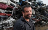 Adam Weitsman stands in front of a pile of cars at his shredding plant in Owego.