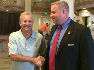 John Kotsianas, left, of Knoxville, Tenn., a sales representative for Stickley Furniture, shakes hands with Paul McNeil, general manager of the Hotel Syracuse, soon to be renamed the Marriott Syracuse Downtown. Kotsianas was the first guest to check into the hotel since its $70 million restoration.