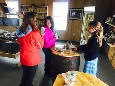 Dan Palladino's daughter, Natalia, right, helping customers sample items in the farm's new Food Store.