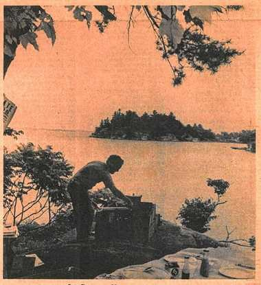 Fishing guide Joe Garnsey prepares a traditional shore dinner at the Thurso Bay Point, Grindstone Island Old Guide Grounds in 1979.