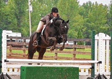 Paige Pavlot riding her show horse Jak. Jak won first place in this show.