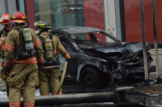 Syracuse firefighters stand near a toppled light pole and charred car Friday afternoon on South West Street in Syracuse near the West Fayette Street intersection. The car caught fire after crashing into a light pole.