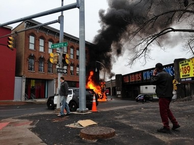 A car burns after crashing into a pole Friday on South West Street in Syracuse near the West Fayette Street intersection.