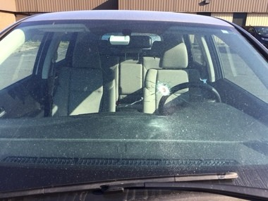 A bullet hole is visible in the windshield of this Honda SUV parked across the street from 1226 E. Fayette Street. The back window was also shattered, and blood was visible underneath a broken sideview mirror.