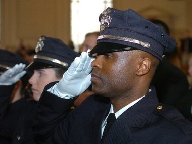 Syracuse police officer Vallon Smith salutes the flag during the beginning of swearing-in ceremonies when he and 15 other officers were hired in 2005.