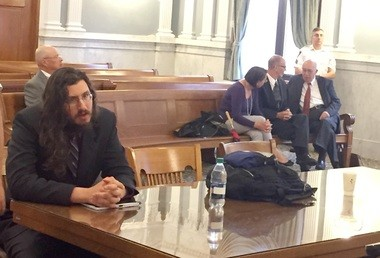Michael Rotondo, left, sits during an eviction proceeding brought by his parents, Mark and Christina, of Camillus. The two parents confer with their lawyer, Anthony Adorante (far right), in the court gallery behind.