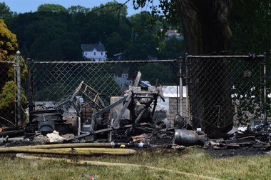 A fire razed a shed Wednesday afternoon in Syracuse, spreading to two homes in the 600 block of Hazelwood Avenue. Charred lawn supplies were left behind.
