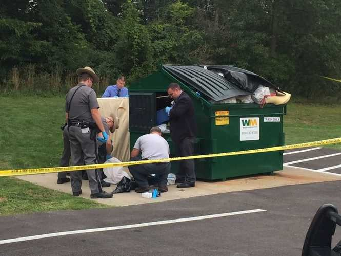 Troopers and investigators look through a garbage dumpster at the Willow Woods Apartment Homes (Chris Libonati | clibonati@syracuse.com).