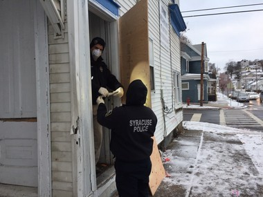 Syracuse police board up the doorway to an apartment where a 16-year-old was shot and killed Monday night.