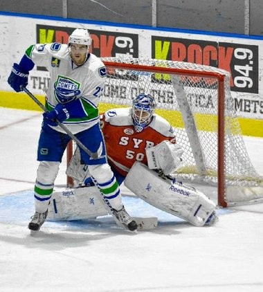 Utica Comets forward Tom Sestito screens Syracuse Crunch netminder Kristers Gudlevskis in a game Dec. 13 in Utica.