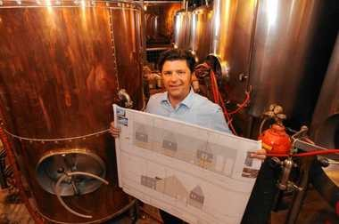 Empire Brewery owner David Katleski holds an architectural drawing for a new farm brewery in Cazenovia that will break ground this summer. He was photographed inside the brewhouse at the Empire brewpub on Walton Street in Armory Square.