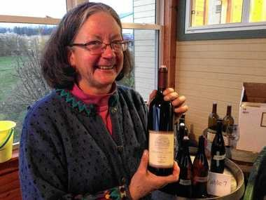 Standing Stone Vineyards co-owner Marti Macinski with a bottle of its 2013 Saperavi, a dark red wine.