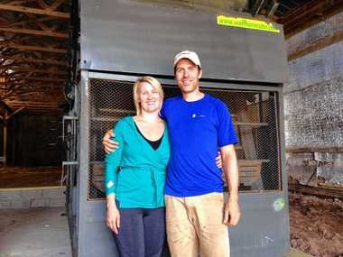 Kate Brodock and Chad Meigs in front of the German-made Wolf hop harvester at The Bineyard, their hop business in Cazenovia.