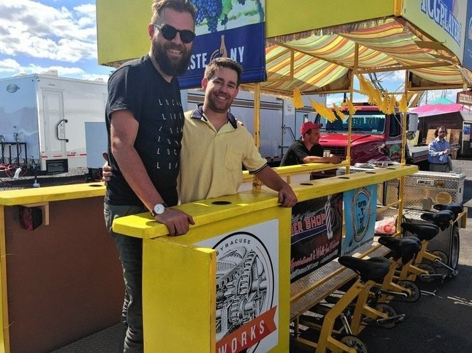 Michael John Heagerty and Mike Giannasttasio on the Big Yellow Fellow pedal-powered pub.