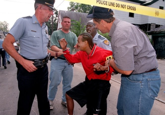 Clifford Ryans is restrained by police in this 1999 photo from the scene of his son's shooting death.