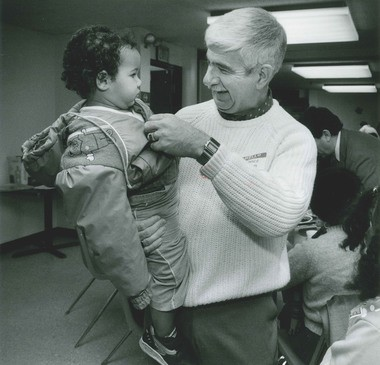 Rescue Mission director Clarence Jordan helps 18-month-old Tammy Jones with her coat on Dec. 25, 1991. Tammy was one of those left homeless by an apartment fire on Bellevue Avenue the day before.