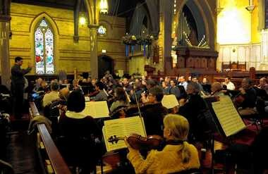 The musicians of Symphoria practice in St. Paul's Cathedral. The IRS approved the orchestra's request for not-for-profit status.