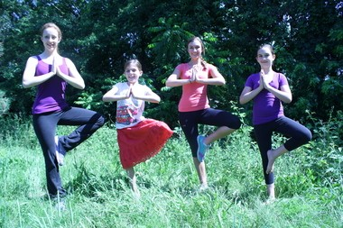 """Four young students demonstrate Vrikshasana, the """"tree pose,"""" which teaches balance while toning the muscles of the legs."""