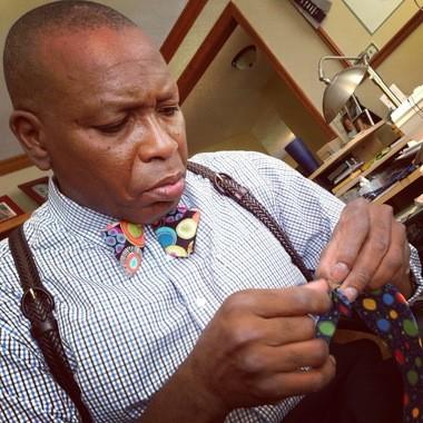Geraldo De-Souza demonstrates how to tie a bow tie at his East Syracuse home.