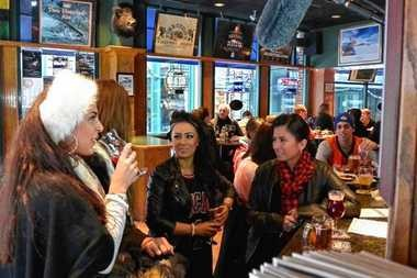 Gloria Rakowsky of Syracuse, right, has beers with two members of the British show 'Campus Crashers' at The Blue Tusk in Syracuse.