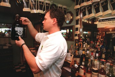 John Andrews, a bartender at the former MacGregor's Grill & Tap Room, checks the level of Ellicottville Ale inside the jug before capping it. Today, J.Ryan's Pub occupies the building.