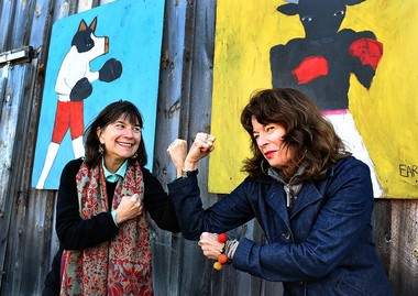 "The NPR's Kitchen Sisters, Nikki Silva (left) and Davia Nelson have fun posing in front of the pig and cow in boxing gloves paintings during the ""Oink vs. Moo"" LongHouse Food Revival."