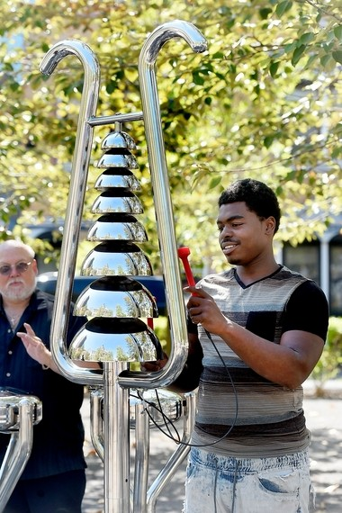 Symphoria demonstrates weather-resistant outdoor instruments that will be installed along Columbus Circle. Naquee Chavers, of Syracuse, plays the Bell Lyre.