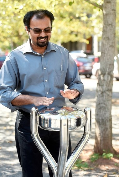 Symphoria demonstrates weather-resistant outdoor instruments that will be installed along Columbus Circle. Chak Rajendran, of Liverpool, tries the Babel Drum.