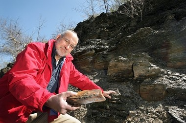 """In his """"day"""" job: Syracuse University professor Donald Siegel examines a sample of Marcellus Shale at an outcropping on Rt. 174 in Marcellus."""