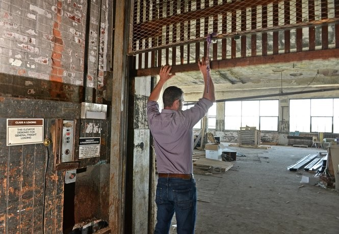 Rick Destito renovated The Gear Factory, a 65,000 square foot building which was once home to the Brown-Lipe Gear Co. Rick opens the freight elevator gate. Tuesday, June 21, 2016.