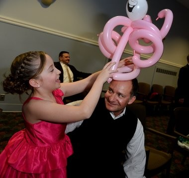 Father-Daughter Valentine Ball benefiting the Upstate Golisano Children's Hospital takes place at the Art & Home Center on the NYS Fairgrounds, Tue. Feb. 9, 2016. Sofia Bregande of Manlius puts a balloon hat on her dad, Mark Bregande.